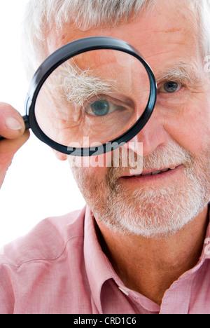 retiree with loupe - Stock Photo