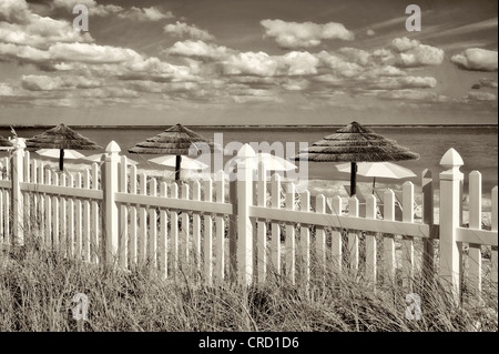 White picket fence and beach umbrellas. Grace Bay. Providenciales. Turks and Caicos - Stock Photo