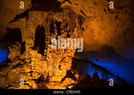 Colorful light lines the way through the THIEN CUNG CAVE system near HALONG BAY, Vietnam - Stock Photo