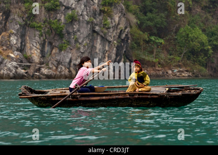 A young VIETNAMESE girl rows her sister in a small boat on the waters of HALONG BAY, Vietnam - Stock Photo