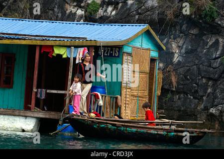 A family and their small floating home in a fishing village, Vietnam, Halong Bay - Stock Photo