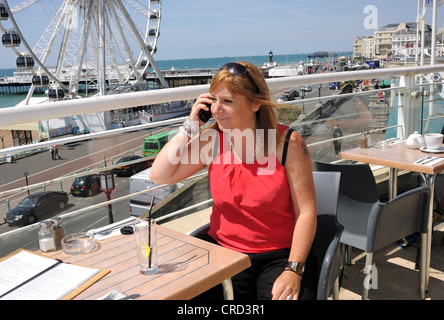 Woman enjoying a drink at seafront cafe bar near the Wheel of Excellence Sussex UK using mobile phone to make a - Stock Photo
