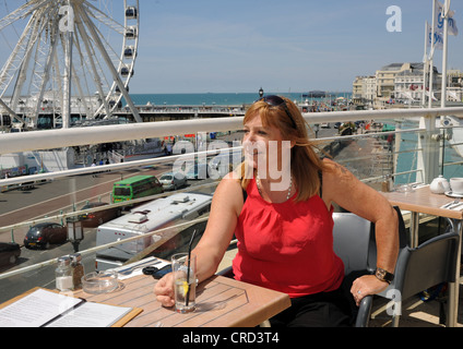 Middle aged woman enjoying a drink at seafront cafe bar  The Terraces near the Wheel of Excellence Sussex UK - Stock Photo
