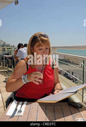 Woman enjoying a drink at seafront cafe bar called The Terraces choosing from menu Brighton Sussex UK - Stock Photo