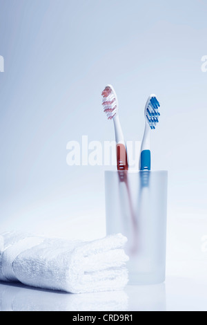 Toothbrushes in toothbrush tumbler beside white towel - Stock Photo