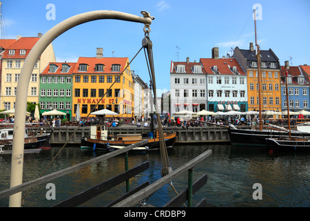 The Nyhavn canal and entertainment quarters in the port of Copenhagen seen through a wooden gangway hanging from - Stock Photo