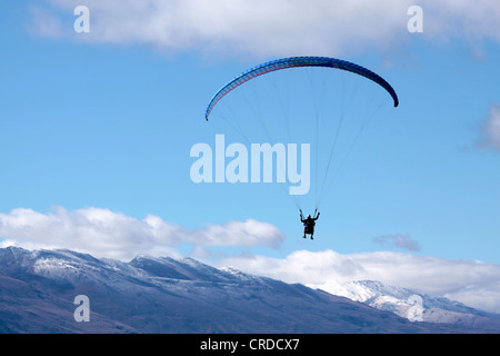 Paraglider in the mountains at Bobs Peak, Queentown, Otago, South island, New Zealand - Stock Photo