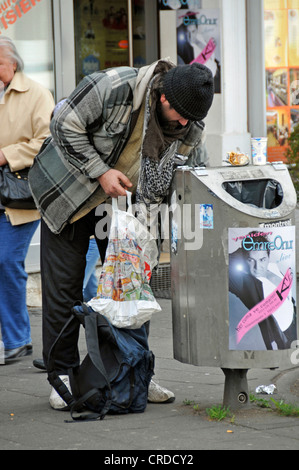 homeless person searching a trashcan, Germany, North Rhine-Westphalia, Koeln - Stock Photo