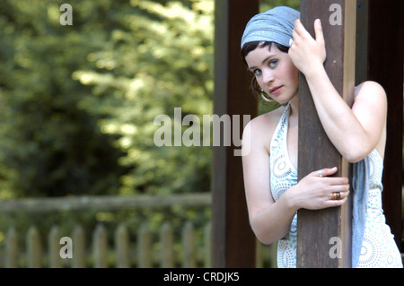portrait of a beautiful woman with headress, leaning on a post, Germany - Stock Photo