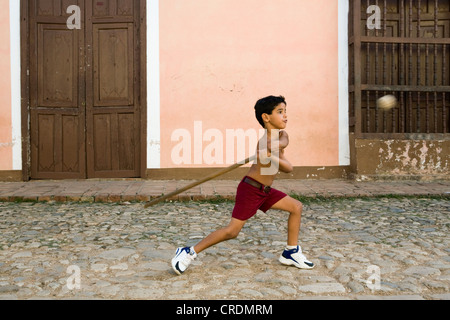 Boy playing baseball in the streets of the old town of Trinidad, Cuba - Stock Photo