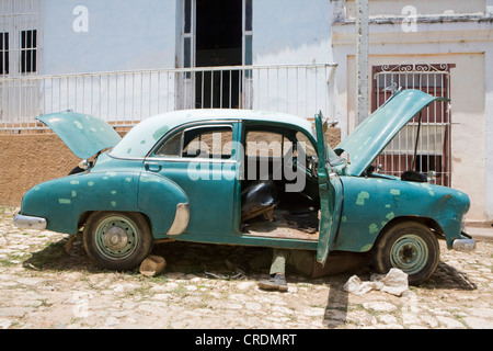 Man lying under a classic American car in street in the old town of Trinidad, Cuba - Stock Photo