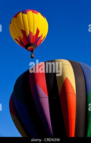 Hot air balloon rising into clear blue sky. - Stock Photo