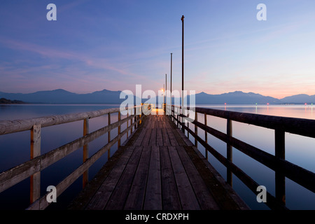 Jetty in Seebruck on Chiemsee lake overlooking the Chiemgau Alps at dusk, Bavarian Alps, Bavaria, Germany, Europe, - Stock Photo