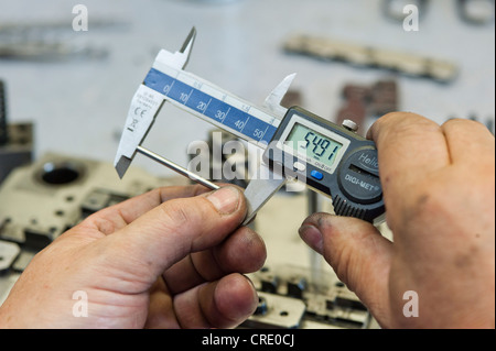 Taking a measurement with calipers, tool production - Stock Photo