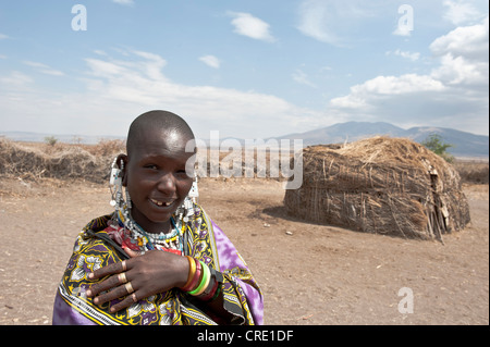 Portrait, ethnology, Maasai woman wearing jewellery, Maasai, bald, shaved head, in front of Hut made of Straw and - Stock Photo