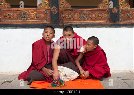 Tibetan Buddhism, three novices sitting on the ground wearing red robes, Rinpung Dzong Monastery and Fortress, courtyard, - Stock Photo