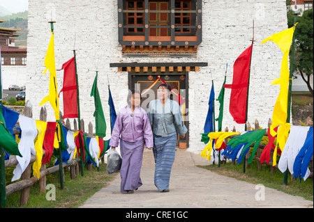 Two women dressed in traditional costume, coloured flags lining a path, fortress-monastery, Dzong, Punakha, the - Stock Photo