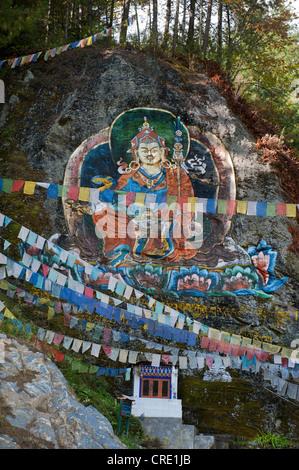 Colourful rock painting, petroglyphs, Guru Rinpoche, Padmasambhava, colourful prayer flags, near Thimphu, Kingdom - Stock Photo
