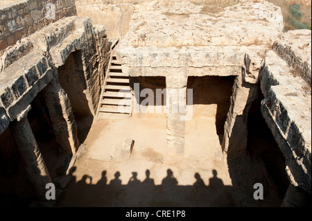 Shadows of tourists on a study trip, looking down into a tomb, Royal Tombs, archaeology, Paphos, Pafos, Cyprus, - Stock Photo