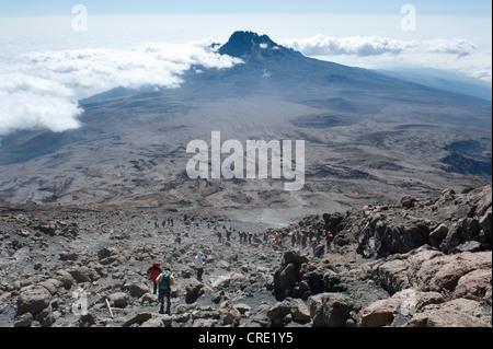 Trekking, mountain climbing, view from the crater rim towards climbers descending towards Kibo Hut at the Kibo Saddle, - Stock Photo