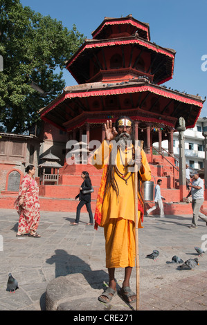 Portrait, holy man wearing glasses blessing with his hand, Mudra, Sadhu, brightly painted forehead, orange robe, - Stock Photo