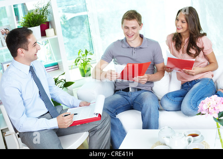 Financial agent holding a meeting with a young family at home discussing the terms of the contract - Stock Photo