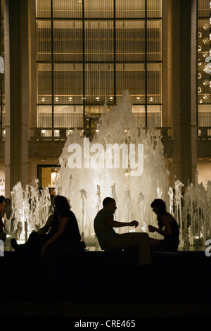 People gathered around the fountain in the main COURTYARD of LINCOLN CENTER at night, USA, New York City - Stock Photo