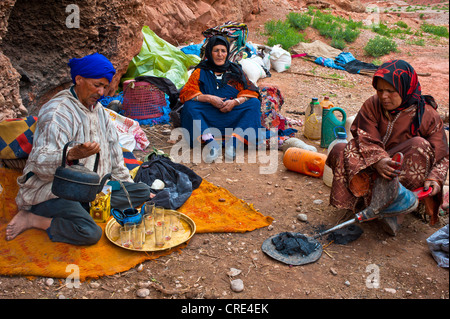 Nomadic cave-dwellers, Berber, a man wearing a blue turban is pouring a cup of tea, a woman is using bellows to - Stock Photo