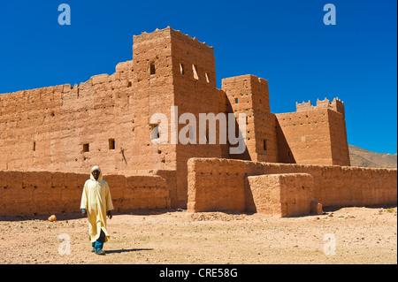 Berber man wearing a traditional djellabah walking in front of Taouirt Kasbah, mud fortress, mud brick building - Stock Photo
