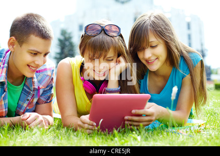 Teenagers being carried away with the staff displayed on the screen - Stock Photo