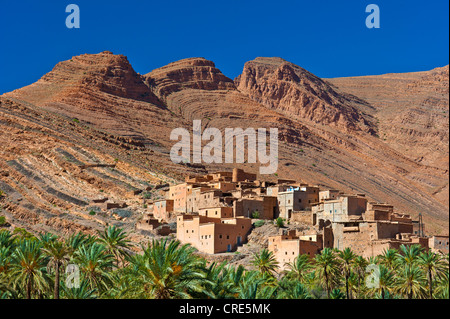 Typical cuesta landscape, mountain slopes characterized by erosion, with small settlements and date palms, Ait Mansour - Stock Photo