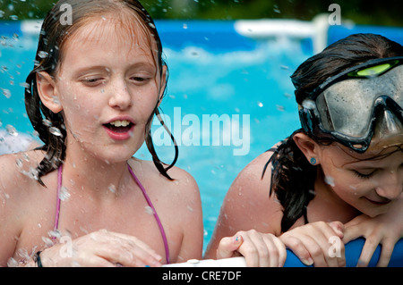 Two young girls in above ground pool - Stock Photo