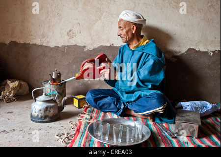 Elderly Berber man wearing a turban sitting on the floor on a rug preparing traditional mint tea, kindling the fire - Stock Photo