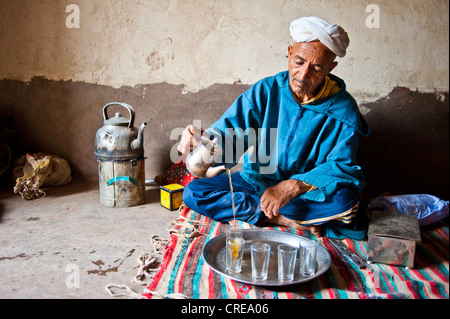 Elderly Berber man wearing a turban sitting on the floor on a rug pouring traditional mint tea from a silver jug, - Stock Photo