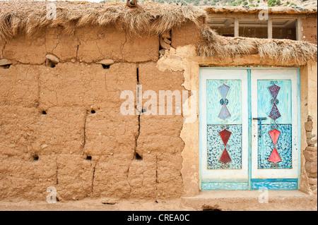 Facade made of adobe bricks, typical ornamental metal door, painted, Ait Bouguemez Valley, High Atlas Mountains, - Stock Photo