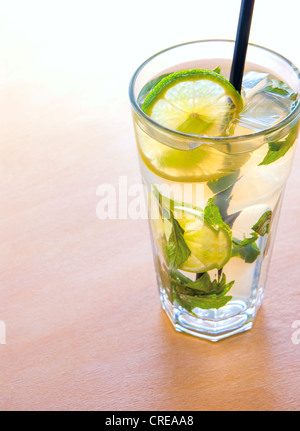 mojito cocktails with lime, mint leaves and ice on wooden placemat background - Stock Photo