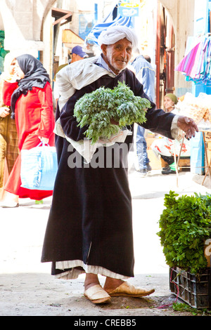 Man wearing a traditional djellaba for his shopping at the market or souk in the historic town or medina - Stock Photo