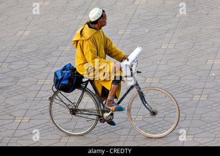 Man wearing a traditional djellaba riding a bicycle in Djemaa El Fna square, medina or old town, UNESCO World Heritage - Stock Photo