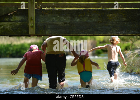A family enjoying the water at Figheldean Mill Pond, Wiltshire UK - Stock Photo
