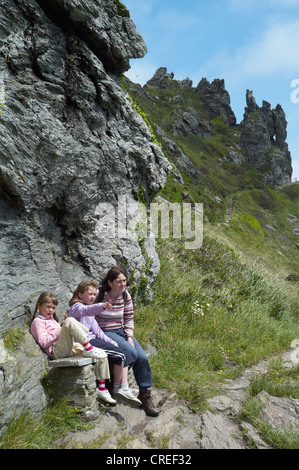 mother and two children sit on a bench near Salcombe harbour at bolt head on the south west coast path south devon - Stock Photo