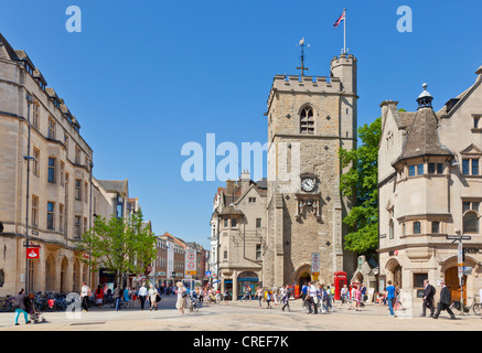 Shoppers in Oxford city centre with Carfax tower at Junction of High street Queen street St Aldates and Cornmarket street UK GB UK Europe Stock Photo