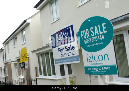 New houses and house for sale signs at The Limes in Plymouth Devon - Stock Photo