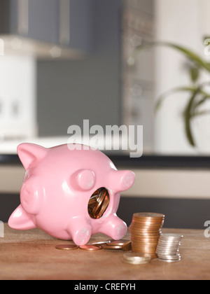 Piggy bank with coins on table - Stock Photo
