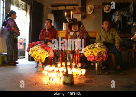 Maya saint Maximon in the living room with Maya Indians in typical costume, Guatemala, Atitlansee, Santiago de Atitlan - Stock Photo