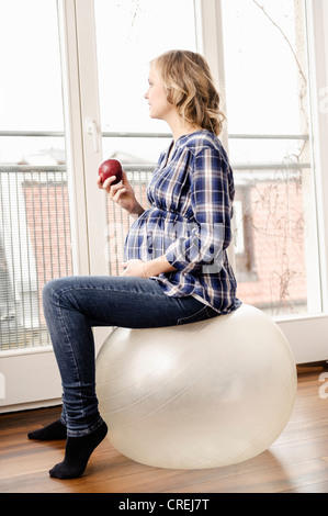 Pregnant woman sitting on exercise ball - Stock Photo