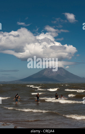 People walking on the shallow shore of Lago de Nicaragua, volcanic island of Ometepe and the stratovolcano Volcán - Stock Photo
