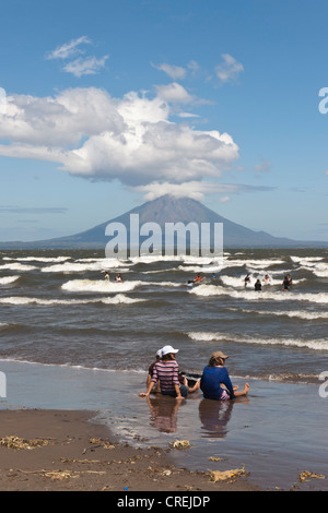 People sitting on the shallow shore of Lago de Nicaragua with the volcanic island of Ometepe and the stratovolcano - Stock Photo