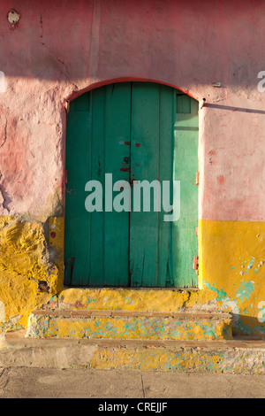 Green door and crumbling wall painted in pastel colors, Granada, Nicaragua, Central America - Stock Photo