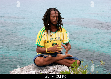 Rasta man with Rasta curls and shirt in the national colors meditating on a stone at the shore, Jamaica, Westmoreland - Stock Photo