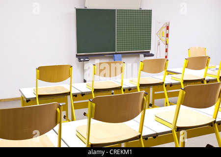 Chairs on desks in a classroom in a school in Straubing, Bavaria, Germany, Europe - Stock Photo